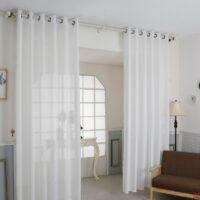 חדר עם ספה, מנורה עומדת ווילונות לבנים